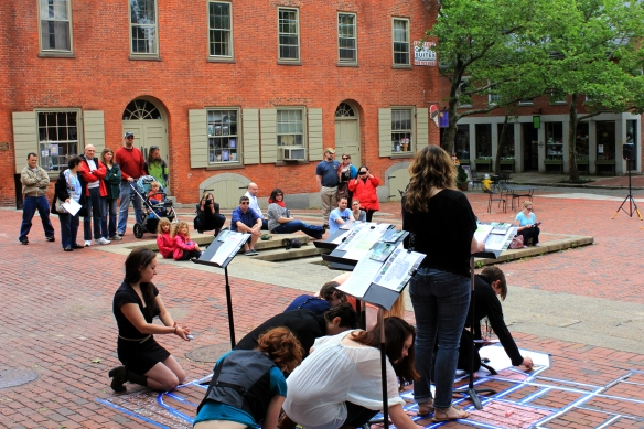 The performers read several rounds of the stories as they fill in the neighborhood blocks with chalk.