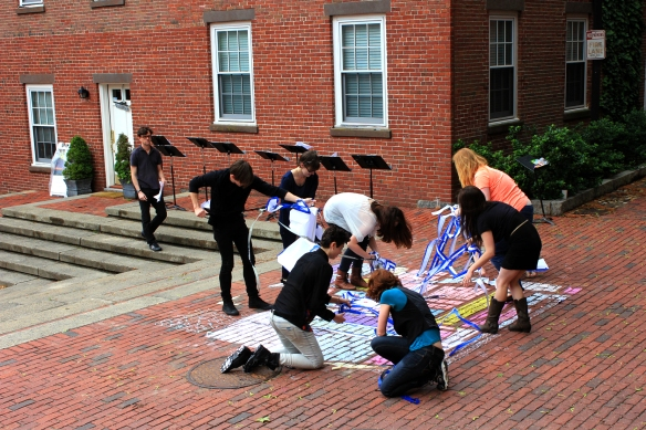 The performers finished chalking in the neighborhood map and began lifting up the paper template.